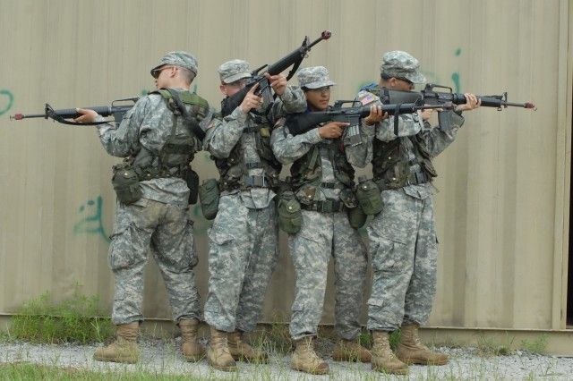 Soldiers prepare to secure a building at the Military Operations in Urbanized Terrain training site at Fort Jackson.