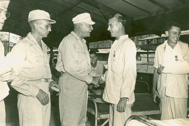 Brigadier General Elmer F. Wallender congratulating Lieutenant Bernowsky of Sturgeon Bay, Wisconsin, upon receipt of his Purple Heart. Photograph taken March 21, 1945, at Hollandia, Dutch New Guinea.(Henry Utley Milne Collection).