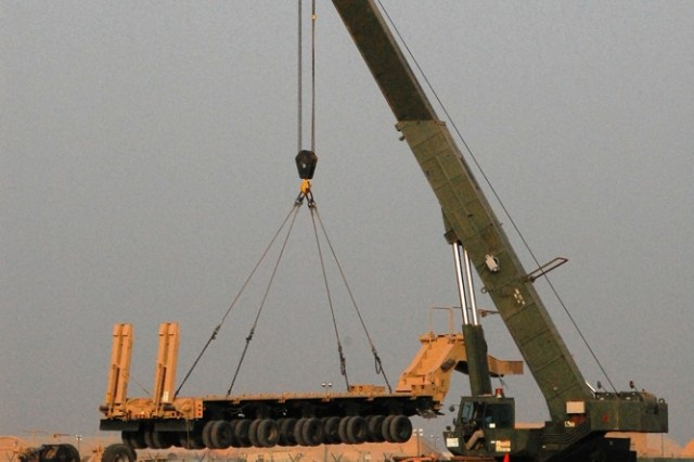 Using a 75-ton capacity, RT 875 Rough Terrain Crane, workers at Camp Arifjan, Kuwait load a recently refurbished M1000 Heavy Equipment Transport Trailer for transport north in support of Operation Iraqi Freedom. The M1000 weighs in at 25 tons and has a payload-carrying capacity of 70 tons.