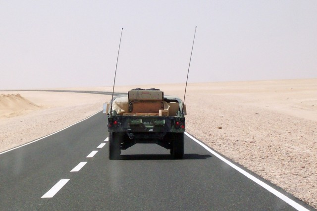 The open road and surrounding desert seem to swallow up a Humvee on the way to Camp Beurhing, Kuwait, July 29, 2008.