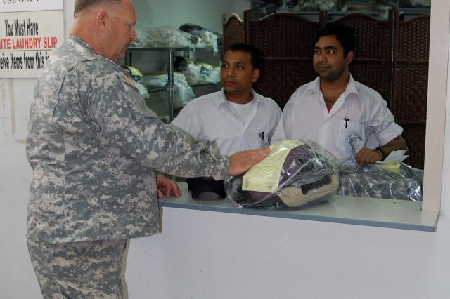 Ron Abner, force protection officer, 401st Army Field Support Brigade, talks with Kuwait Pritchard Laundry Service employees Nazrul Islam (L) and Abdul Hai, as he picks up a load of laundry from the AIK Laundry Facility at Camp Arifjan, Kuwait, Saturday, August 2, 2008.  The laundry provides three day service and is open daily from 7 a.m. to 6:30 p.m. for service members and DoD civilian employees. Islam and Hai are from Jessore, Bangladesh.