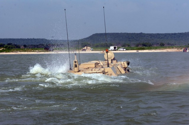 """Soldiers from Headquarters and Headquarters Company, 1st Brigade Special Troops Battalion, 1st Brigade Combat Team, 1st Cavalry Division, thrust forward during a training exercise to test their M93 """"Fox"""" vehicle at Blora Lake, Texas on July 31.  The six-wheeled """"Fox"""" is an amphibious laboratory that takes air, water and ground samples and immediately analyzes them for signs of weapons of mass destruction."""