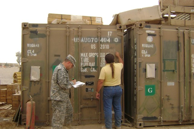 Capt. Richard Crawford, Lean Six Sigma Green Belt with the 1182nd Transportation Terminal Battalion, works with a container inventory team member at a forward operating base in Iraq.