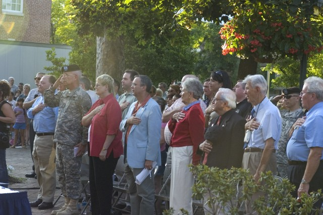 A mixed audience of community members and Army War College students signal respect as The Volunteers' singer leads the national anthem during the Carlisle-Carlisle Barracks Community Covenant signing ceremony Aug. 1.
