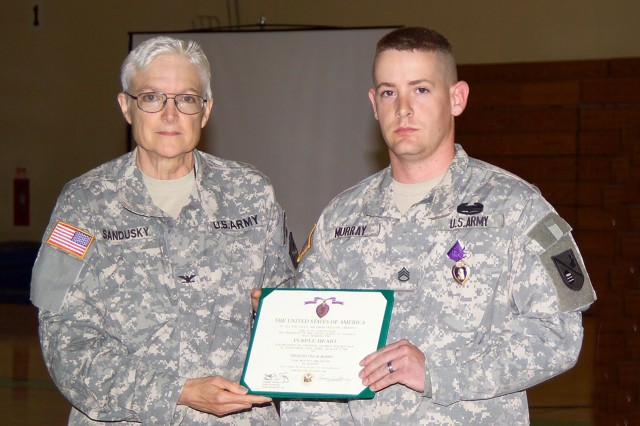 Purple- Col. Sue Ann Sandusky gives Staff Sgt. Eric Murray his Purple Heart after over a year since his deployment for Operation Enduring Freedom.  Murray had sustained a bullet wound in his right leg while attempting to pull a wounded Soldier to safety during a firefight.