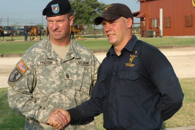 During his visit to Fort Hood, Texas, Sgt. Maj. of the Army Kenneth O. Preston (left) poses for a photo with McEwen, Tenn. native Spc. Buck Albritton of the Horse Cavalry Detachment, 1st Cavalry Division at the Horse Cavalry Detachment stables Aug. 4.