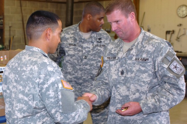 Taking the opportunity to meet with and talk to 1st Cavalry Division Soldiers, Sgt. Maj. of the Army Kenneth O. Preston (right) presents a coin to El Centro, Calif. native Pvt. John Preece, a tanker with Company D, 3rd Battalion, 8th Cavalry Regiment during an Aug. 4 visit to Fort Hood, Texas