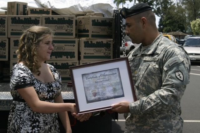 SCHOFIELD BARRACKS, Hawaii - Maj. Adelaido Godinez, rear detachment commander, 2nd Stryker Brigade Combat Team, presents 16-year-old Sascha Franzel with a certificate of appreciation. Franzel gathered 1000 aloha shirts through community donations to send to Soldiers in Iraq.
