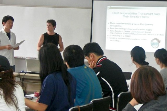 Yongsan bodybuilding champ Tracey Briggs (standing right) teaches a class on fitness and bodybuilding to students at Tongwon College southeast of Seoul. Briggs presented the four-hour lecture to students who may someday become professional fitness trainers.