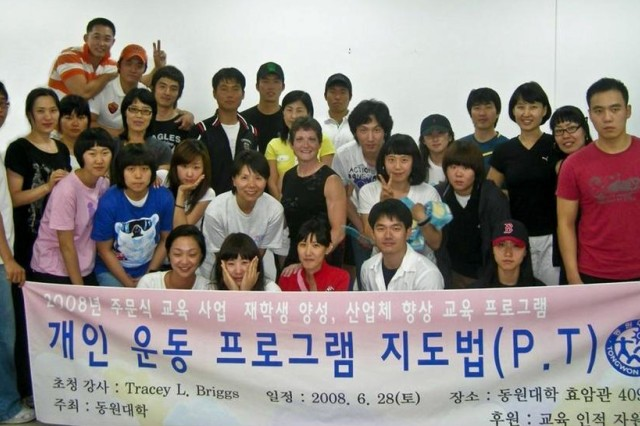 Yongsan bodybuilding champ Tracey Briggs (center) stands with students from Tongwon College southeast of Seoul after presenting a lecture on fitness and bodybuilding. Briggs presented a four-hour class on fitness and bodybuilding to students who may someday become professional fitness trainers.