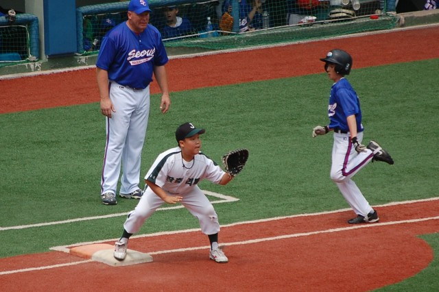 Seoul Baseball Club player Nathan Simpson, 13, runs to first during an SBC little league game in June at the Chungjang Stadium in Seoul. Coach Russell Bruce stands at first base.