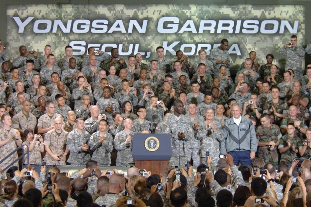 President George W. Bush stands beside U.S. Forces Korea Commander Gen. Walter Sharp (left) and Cpl. Victor L. Berlus, Eighth United States Army, on stage Aug. 6, before addressing military personnel, Families, and Department of Defense Civilians at Yongsan Garrison, Seoul, Republic of Korea. As the U.S. Eighth Army Non-Commissioned Officer of the Year for 2008, Berlus had the honor of introducing the president to the standing-room-only audience. - U.S. Army Photo By Edward N. Johnson