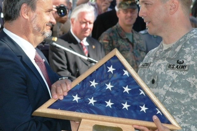 """Lt. Col. David Astin, commander of U.S. Army Garrison Darmstadt, Germany, presents an American flag to Darmstadt Lord Mayor Walter Hoffmann. The inscription read: """"To The City of Darmstadt, flown In freedom and friendship over Cambrai-Fritsch Kaserne."""" The gesture was part of USAG Darmstadt inactivation ceremonies held Aug. 5."""