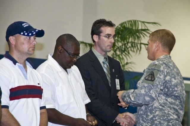 At the 100th Stryker vehicle acceptance event on August 5 at Anniston Army Depot, (l-r) depot mechanic Kenny Duncan, quality specialist Don Allen, and Chris Hewett, depot program manager for the Stryker, receive a coin from the Project Manager for Stryker Brigade Combat Team Col. Robert Schumitz.