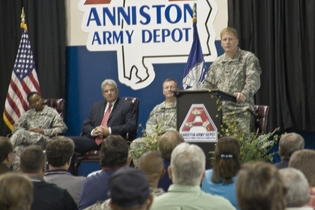 Col. Robert Schumitz, Project Manager for Stryker Brigade Combat Team, comments August 5 on the 100th Stryker repaired at Anniston Army Depot. Also on stage in the official party are (l-r) Depot Commander Col. S. B. Keller, General Dynamics' Don Ishmael, DCMA's Col. Daniel Gallagher and (not shown) Jack Cline, deputy to the commander.