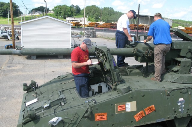 Depot mechanics Mark Epps (left) and Patrick Webber (middle) work alongside General Dynamics engineer Jeff Monroe to perform a limited technical inspection in June on a Stryker mobile gun system before it\'s reset to like-new condition at Anniston Army Depot. A Stryker MGS model like this one turned out to the 100th Stryker repaired at the depot.