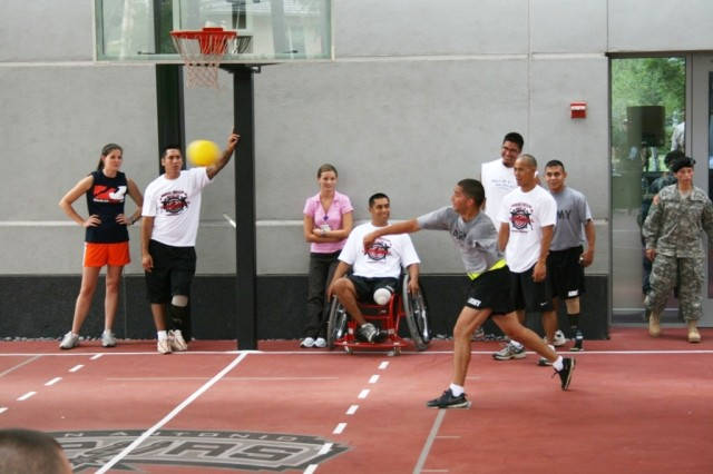 """Disco Knights"" player Domingo Soto-Santana hurls the ball at an opponent at the Warrior Transition Battalion Dodge Ball Tournament July 30 at the Center for the Intrepid's outdoor sports court."