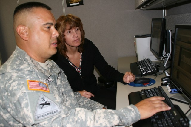 Gabriele Dias, Army Continuing Education System education counselor, helps Warrior in Transition Staff Sgt. Juan Rodriguez navigate GoArmyEd, an online education resource for Soldiers, at the Soldier and Family Assistance Center.