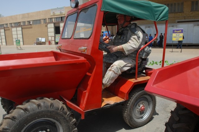 Lt. Cdr. James Harper, a member of the agriculture team assigned to Multi-National Force CJ9, checks out a front-load dumper, which has a 1.1-ton capacity, during the business exposition at the Iskandariyah Industrial Complex Aug. 3.