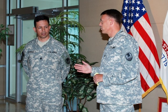Col. Bruce Smith, Director of Combat Development, right, welcomes home Lt. Col. Tony Chavez from a year long deployment to Afghanistan. Chavez's sister, Christella and his girlfriend, Crista Benavidez were in attendance at the Jul. 31, welcome home ceremony.