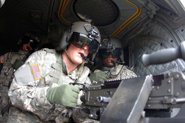 Sgt. Chris Scharff (left) and Gaithersburg, Md., native Sgt. Emilio Green (right), both flight engineers for Company B, 2nd Battalion, 227th Aviation Regiment, 1st Air Cavalry Brigade, 1st Cavalry Division, observe as St. Paul, Minn., native Chief Warrant Officer 2 Stephen Crews (center), a CH-47F Chinook pilot, fires an M60 machine gun from the new F-model Chinook during an aerial gunnery at Fort Hood, Texas, July 16. One of the upgrades that affect the crewmembers in back of the F-model is the improved communications systems. Now, flight engineers are able to communicate between other aircraft and the ground instead of just within their own plane, said Scharff who hails from Brevard, N.C.