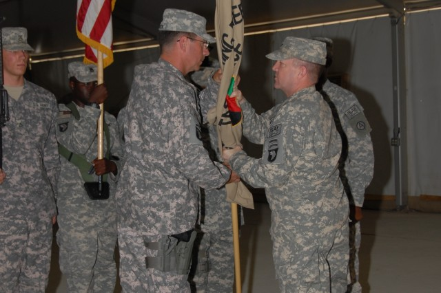 Col. Thomas D. Vail, CJTF 101 chief of staff, presents the Task Force Anzio unit colors to Col. Ralph W. Haddock, the incoming U.S. National Command Element (Task Force Anzio) commander, during a change of command ceremony Aug. 6 at Kandahar Air Field.