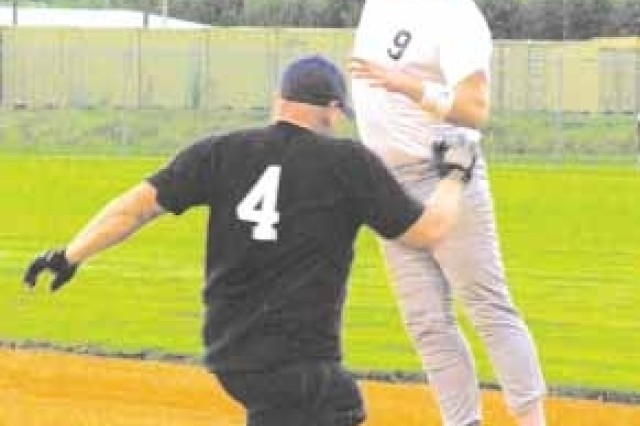 Co. A, 3rd BSB's Kevin Gregg elevates to try to reach an errant throw as the 514th Engineer Detachment's Tony Fornicola hustles down the first base line.