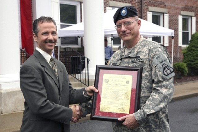 Project Manager for Maneuver Ammunition Systems Chris Grassano presents the Product Manager for Small Caliber Ammunition charter to Lt. Col. Jeffrey Woods during a ceremony at Picatinny Arsenal June 26.