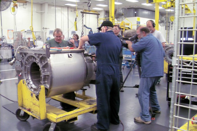 In the Turbine Engine facility, Michael Steen and Hank Jobson mate a Forward Engine Module to the Rear Engine Module.  Al Jazeera English news network members record footage for a future video series.