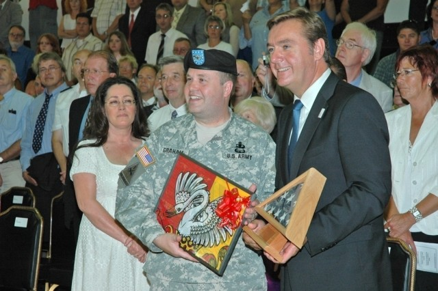 Col. Ray Graham, U.S. Army Garrison Hessen/Wiesbaden commander, and Hanau Lord Mayor Claus Kaminsky display their exchanged gifts during a closure ceremony for USAG Hessen, Germany, Aug. 7.