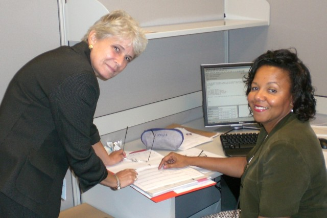 Lynne Caroe (standing) and Anna Carter, new members of the Army Senior Fellows program, prepare for their assignments at the Washington Institute of Near East Policy and Army Diversity Task Force, respectively.
