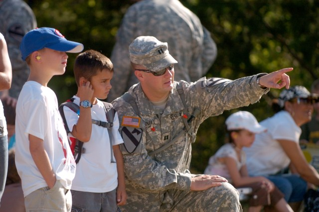 Capt. Tyler Donnel, Battery B commander, points out the Paladin to 9-year-old Bryson Thacker (left) and his son, 7-year-old Devin during the 3rd Battalion, 82nd Field Artillery Regiment, 2nd Brigade Combat Team, 1st Cavalry Division's family day in the field Aug. 7.
