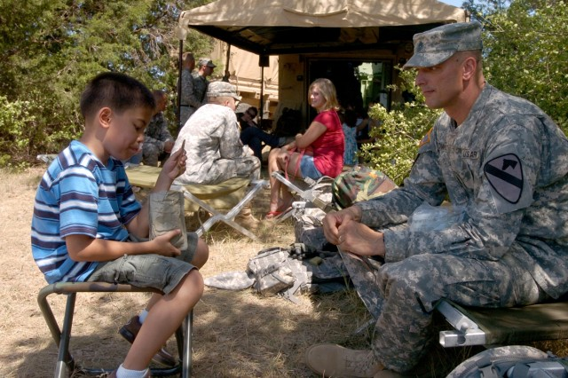 First Sgt. Christopher Towns and his 9-year-old son Anthony share an MRE lunch together during the 3rd Battalion, 82nd Field Artillery Regiment, 2nd Brigade Combat Team, 1st Cavalry Division's family day in the field Aug. 7.