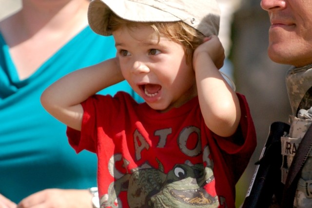 Three-year-old Elias Pratt plugs his ears to the M109 Paladin's blast as he watches with his parents Nina and WO1 David Pratt of Tucson, Ariz. during the 3rd Battalion, 82nd Field Artillery Regiment, 2nd Brigade Combat Team, 1st Cavalry Division's family day in the field Aug. 7.