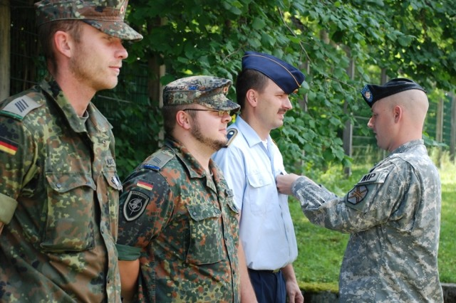 Sgt. First Class Christopher Allison, NCOIC of the U.S. Army Garrison Garmisch, Germany, Provost Marshal office, awards Luftwaffe (German air force) Hauptfeldwebel Michael Meyer and Bundeswehr (German army) soldiers Stabsgefreiter Robert Hüste, left, and Hauptgefreiter Eric Zuther with U.S. Army Weapons Qualification Badges for M-16 rifle and M-9 pistol. Meyer, school sergeant major for the NATO School in Oberammergau, then presented four U.S. Soldiers with the German Schutzenschnur for qualifying with the 7.62 MG3 and 9mm pistol.