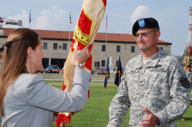 Diane Devens, director of Installation Management Command-Europe, passes the guidon for U.S. Army Garrison Vicenza, Italy, to Col. Erik Daiga during a change of command ceremony Aug. 12.