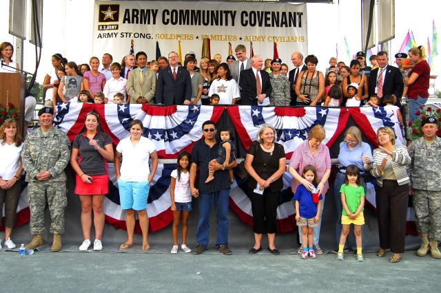 """Members of the Arlington County and Commonwealth of Virginia government, Secretary of the Army Pete Geren, Soldiers and families of the Military District of Washington and the Fort Myer Military Community gather for a group shot Aug. 7 just before signing the Army Community Covenant. The event took place during opening ceremonies at the popular, annual Arlington County Fair. The U.S. Army Band """"Pershing's Own"""" and The Old Guard Fife and Drum Corps started off the festivities with patriotic tunes. """"This is very important for the entire community,"""" said J. Walter Tejada, Arlington County Board Chairman, of the Covenant signing. """"Arlington County only covers about 26 square miles, but it includes the Pentagon, Arlington National Cemetery and Fort Myer. Being so close together, we want to be close partners with the military community."""""""