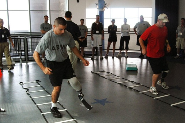 Wounded warriors Staff Sgt. Oscar Guerra and Sgt. 1st Class John Carter set the pace in the ladder drills during the Agility with Prosthesis session at the Military Amputee Advanced Skills Training High Performance workshop July 23 at Brooke Army Medical Center and the Center for the Intrepid. More than 70 physical therapists, prosthetists and physicians attended the workshop July 22 to 24.