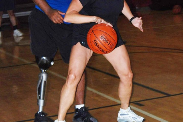 Wounded warrior Staff Sgt. Nathaniel Reed goes all out in guarding a workshop participant during a basketball demonstration between warriors and participants at Fort Sam's Jimmy Brought Fitness Center July 24.