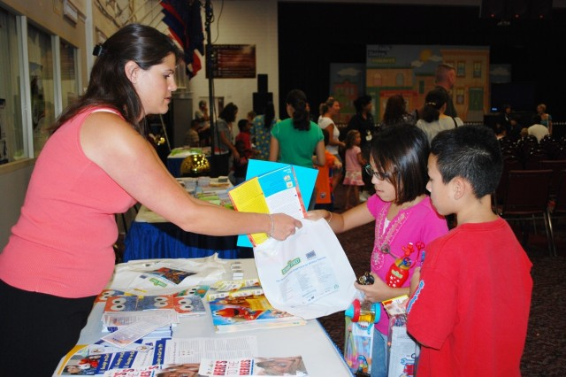 Amanda Moran, of Military OneSource, helps Kassandra Chavez, 11, and her brother José, 9, put beading kits into a bag Aug. 10 at the Fort Sam Houston Army Community Service center. The table was one of many with giveaways and information at the Sesame Street Experience event held Aug. 10 and 11 at ACS.
