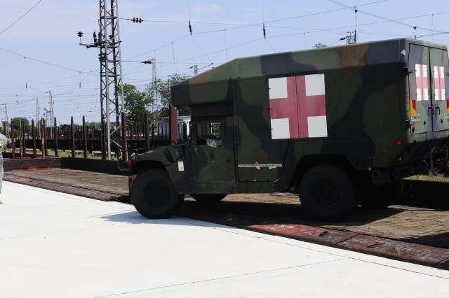 A Soldier ground-guides an ambulance off a rail car during the railhead operation.