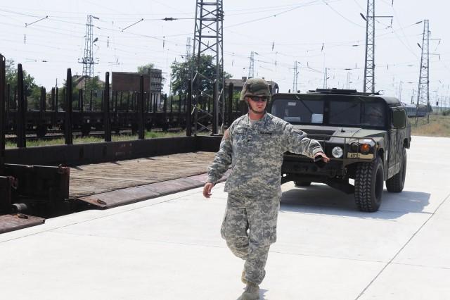 Spc. Derek Mullins guides a vehicle off the unloading platform at the railroad station in Ziminitsa, Bulgaria.