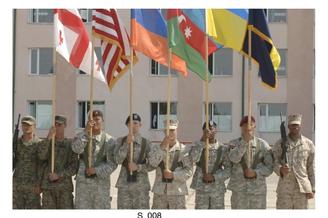"""Soldiers from the U.S. and the country of Georgia display flags from five nations involved with the recent combined exercise """"Immediate Response '08"""" held at the Vaziani military base in the country of Georgia."""