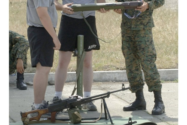A U.S. Soldier checks out Georgian weapons on display during a cultural day between U.S. and Georgian soldiers at Vaziani military base in the country of Georgia.