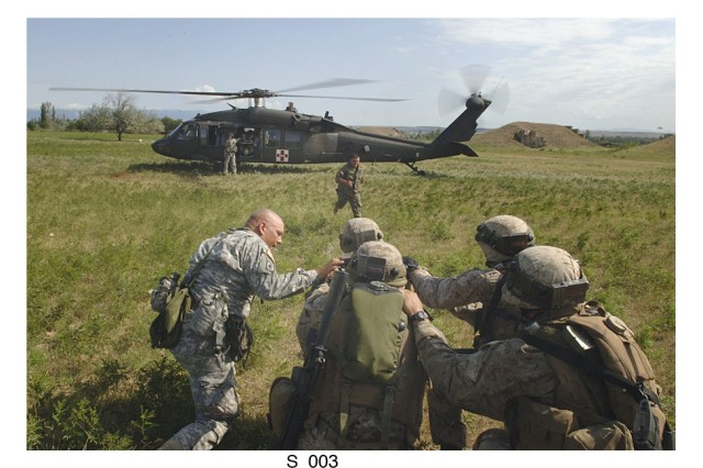 """A U.S. Soldier (left) directs U.S. Marines and Georgian soldiers to a U.S. Blackhawk during a simulated medical evacuation during a combined exercise """"Immediate Response '08"""" held in the country of Georgia late last month."""