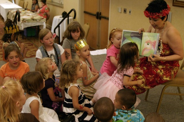SCHOFIELD BARRACKS, Hawaii - CYS Outreach Director Sylvia Scully (right) reads to children during the storytime session at the FMWR expo, Aug. 1. Numerous activities kept children entertained as parents gained information about programs offered through FMWR.