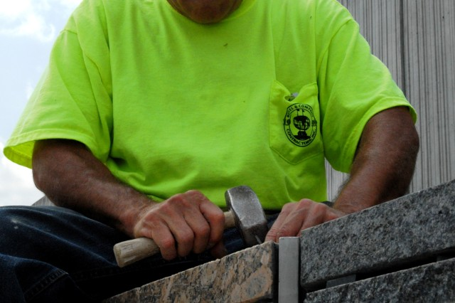 Jose Lopez, a construction worker at the Pentagon Memorial, makes repairs on the granite wall lining the memorial. The project broke ground June 2006 and is scheduled to open during a ceremony next month commemorating the seventh anniversary of the 9/11 attacks.