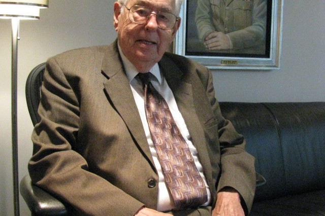 Bill Pittman, who has been an engineer involved in rocket and missile development since coming to Redstone Arsenal in 1951, sits under a portrait of one of his commanding generals, Maj. Gen. Francis McMorrow, commander of the Missile Command from 1962-63. Pittman is the last working engineer from the Army's original rocket team at the Ordnance Missile Laboratories.