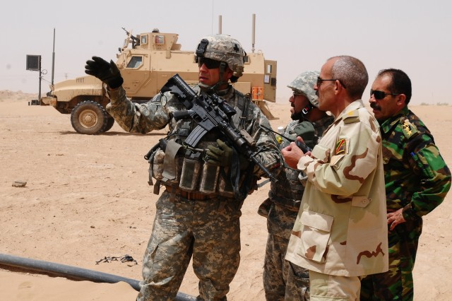 Maj. Oscar Pintado, 1st Battalion, 327th Infantry Regiment Military Transition Team leader, speaks with his Iraqi counterpart during a mission to find weapons caches in the western desert near Bayji, Iraq.