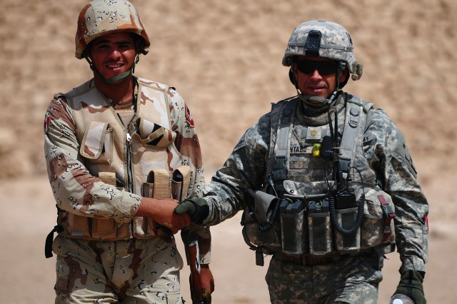 Oscar Pintado, 1st Battalion, 327th Infantry Regiment Military Transition Team leader, shakes hands with an Iraqi Army soldier during a recent mission near Bayji, Iraq. Pintado's MiTT Soldiers are responsible for training and advising two Iraqi Army battalions in the area.